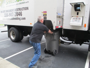 Locked container is emptied into the document shredder by Shamrock Shredding driver